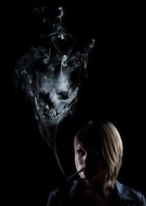 Young women smokes a cigarette and in the smoke appears a deadly skull.